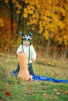Piccolo ragazzo felice in un berretto a maglia e vestiti caldi, stare con la zucca sul prato tra gli alberi di autunno.
