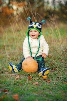 Piccolo ragazzo felice in un cappuccio tricottato che si siede con la zucca sull'erba fra gli alberi e le foglie di autunno di autunno