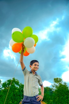 Piccolo ragazzo indiano della scuola che salta nel cielo con gli aerostati di tri colore e che celebra il giorno dell'indipendenza o della repubblica dell'india