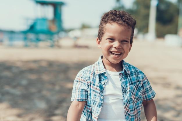 Piccolo ragazzo riccio afroamericano su sandy river beach alone.