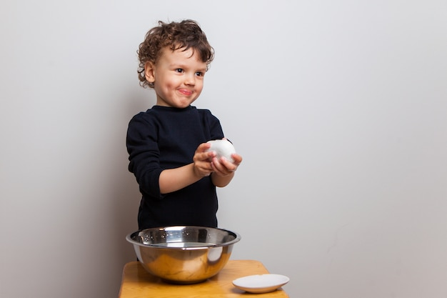Piccolo ragazzo riccio carino è felice di lavarsi le mani con sapone, si lava le mani. procedure igieniche, disinfezione delle mani. prevenzione di malattie con influenza e virus, coronavirus e sars.