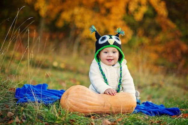 Piccolo ragazzo sorridente con due denti in un berretto a maglia e vestiti eleganti caldi seduti sul plaid blu sull'erba con alberi di zucca e autunno