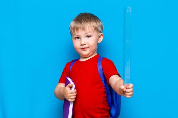 Piccolo ragazzo sorridente felice con gli occhiali sulla sua testa, libro in mano, zainetto sulle spalle. di nuovo a scuola. pronto a scuola