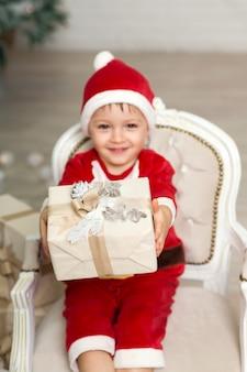Piccolo ragazzo sorridente felice in costume del babbo natale che si siede sulla poltrona vicino all'albero di natale e che tiene il contenitore di regalo di natale
