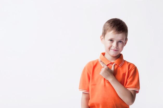 Piccolo ragazzo sveglio che gesturing e che esamina macchina fotografica