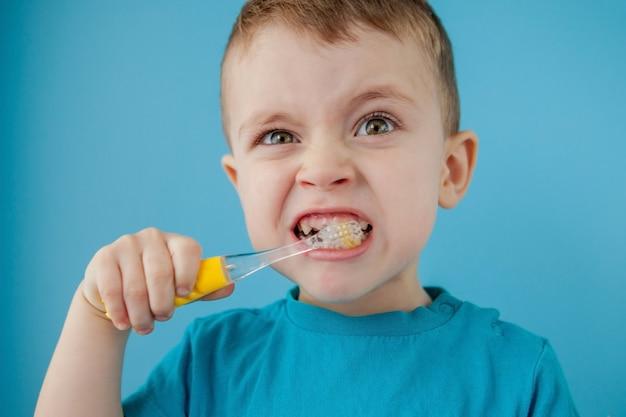 Piccolo ragazzo sveglio che pulisce i suoi denti sulla parete blu