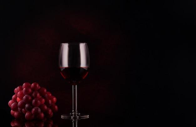 Piccolo ramo di uva e vetro con vino su sfondo nero con riflessi