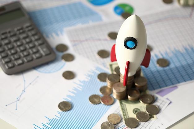 Piccolo razzo del giocattolo, monete, calcolatore e documenti ufficiali allo scrittorio di affari, fuoco selettivo. processo aziendale, profitto, guadagno, concetto di analisi finanziaria