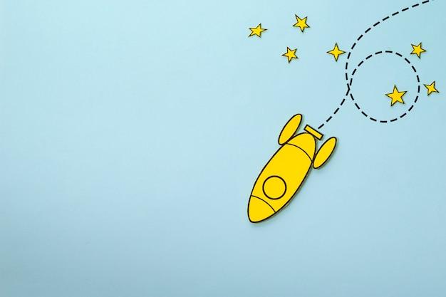 Piccolo razzo giallo che avvolge le stelle sopra un fondo blu