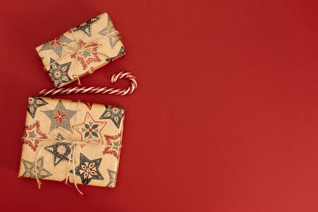 Piccolo regalo con fiocco rosso su sfondo rosso.