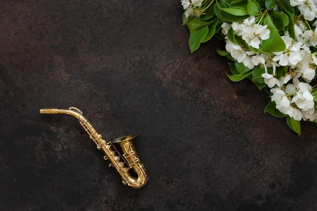 Piccolo sassofono dorato e rami di melo in fiore.