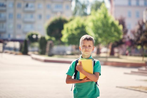Piccolo scolaro sveglio all'aperto il giorno soleggiato. bambino con il suo zaino e in possesso di libri