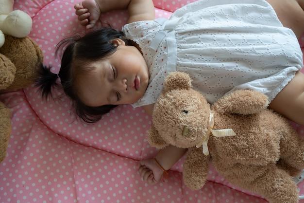 Piccolo sonno asiatico sveglio della neonata