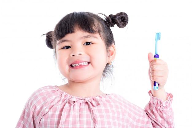 Piccolo spazzolino da denti e sorrisi asiatici della tenuta della ragazza sopra fondo bianco