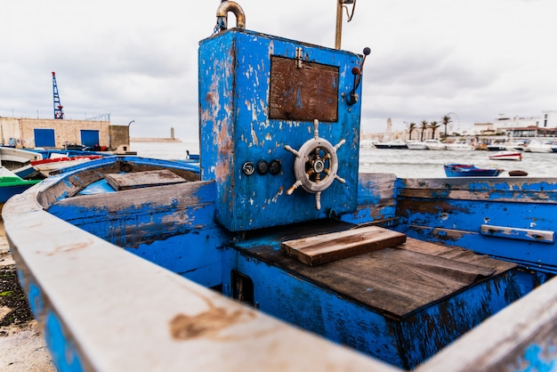 Piccolo timone in legno di una barca spiaggiata invecchiata e abbandonata sulla riva del mare.