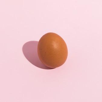Piccolo uovo di gallina marrone sul tavolo rosa