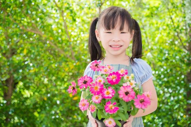 Piccolo vaso di fiore asiatico della tenuta della ragazza e sorrisi in giardino