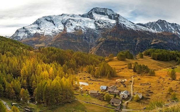 Piccolo villaggio di montagna con alte montagne coperte di neve