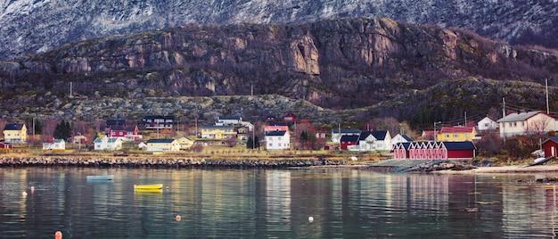 Piccolo villaggio di pescatori ai piedi della montagna con case tradizionali scandinave.