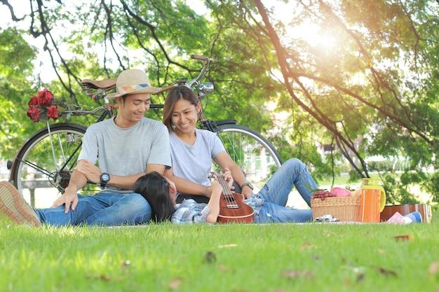 Picnic asiatico felice della famiglia nel concetto di rilassamento di unità del parco