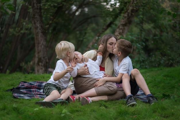 Picnic della famiglia al giardino all'aperto. generi e tre bambini che si siedono sulla coperta di picnic nel parco. la mamma bacia il figlio