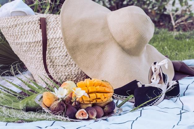 Picnic estivo con un piatto di frutti tropicali.