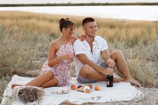 Picnic estivo in riva al mare. gli amanti delle coppie la sera mangiano frutta e bevono vino. serata romantica. proposta di matrimonio