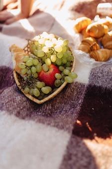 Picnic estivo su un tappeto con frutta, vino e tè, tazze, croissant e dettagli dolci
