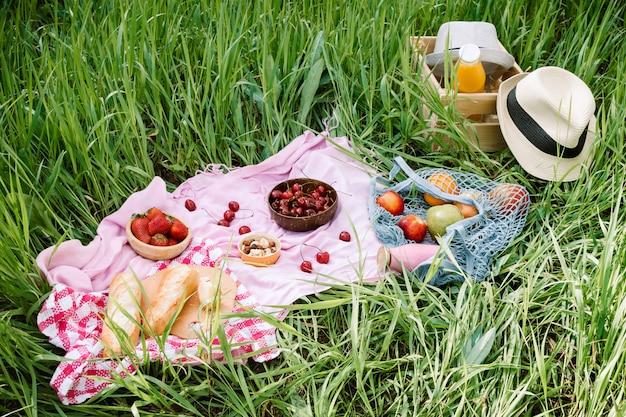Picnic estivo sull'erba con ciliegie, pane fresco e bottiglia di vetro di succo