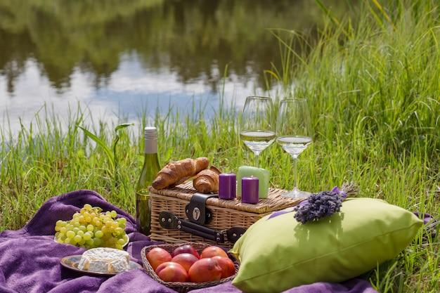 Picnic nella natura in riva al lago: c'è un cuscino sul tappeto viola, un bouquet di lavanda