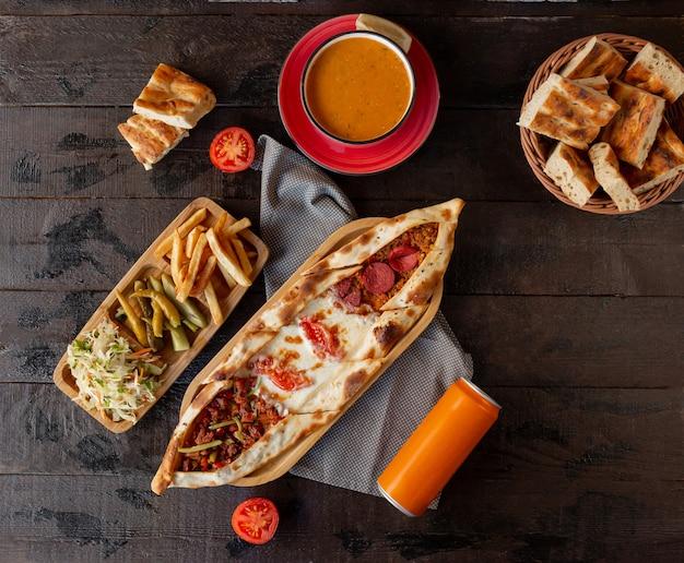 Pide misto con peperoni, formaggio, carne macinata servita con sottaceti e zuppa di pomodoro