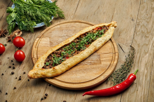 Pide - piatto turco a forma di tortilla con carne di manzo o agnello tritata e cipolle verdi su un vassoio di legno. pizza orientale, ricetta o menu