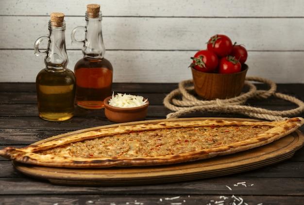 Pide tradizionale turco con carne farcita su una tavola di legno