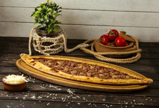 Pide tradizionale turco con formaggio e carne farcita su una tavola di legno