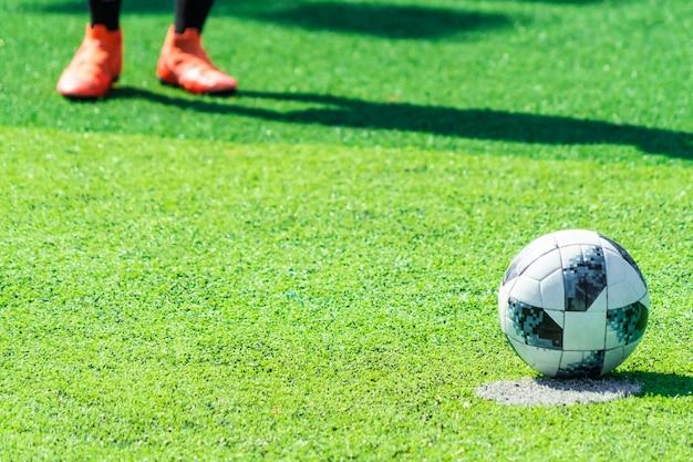 Piede del giocatore di calcio in piedi vicino al calcio di rigore pronto a calciare la punizione sul campo di calcio. determinazione sportiva e concetto impavido.