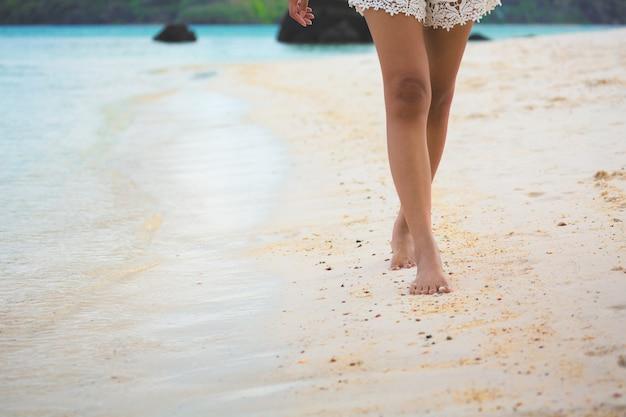 Piede della donna di viaggio sulla spiaggia