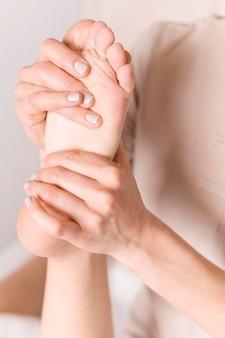 Piede di massaggio della donna del primo piano