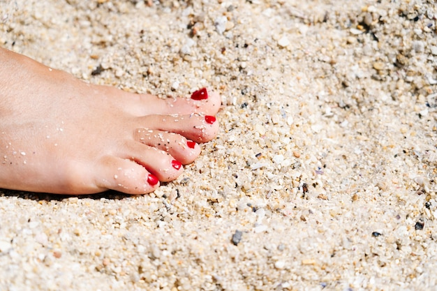 Piede di una donna nella sabbia sulla spiaggia