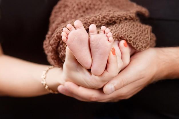 Piedi del bambino nelle mani dei genitori. i piedi del bambino appena nato minuscolo sui genitori hanno modellato il primo piano delle mani. genitori e loro figlio. concetto di famiglia felice.