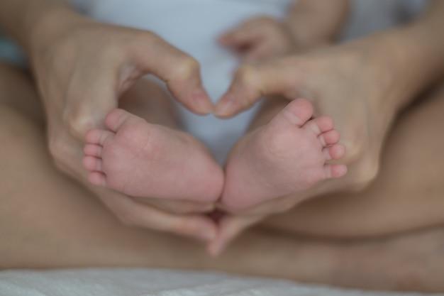 Piedi del bambino nelle mani della madre. mamma e figlia. concetto di famiglia felice. bella immagine concettuale di maternità