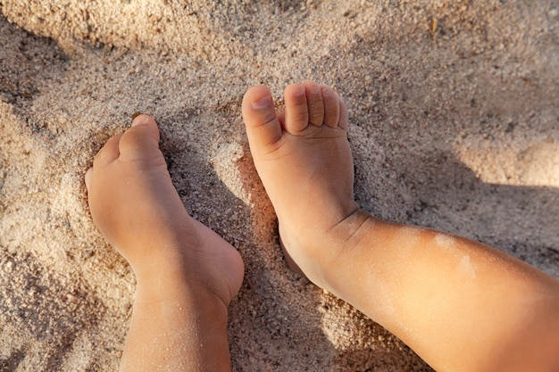 Piedi del bambino neonato sulla spiaggia sabbiosa come concetto di sfondo, infanzia e vacanza