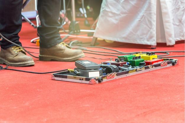 Piedi del chitarrista su un palco con set di pedali effetto distorsione. messa a fuoco selettiva