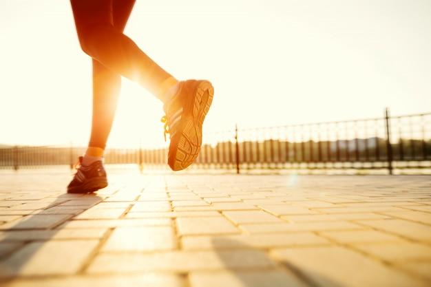 Piedi del corridore che corrono sul primo piano della strada sulla scarpa. concetto di welness di allenamento di jog di alba di forma fisica della donna.