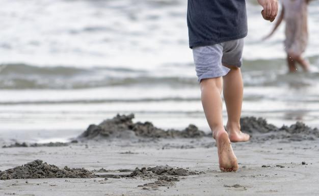 Piedi del ragazzino che corrono su una spiaggia di sabbia