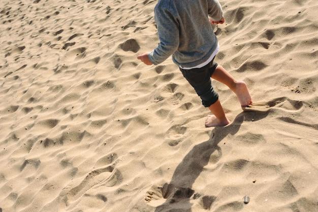 Piedi del ragazzo che cammina sulla sabbia della spiaggia.