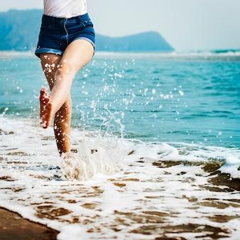 Piedi della donna che spruzza acqua di mare
