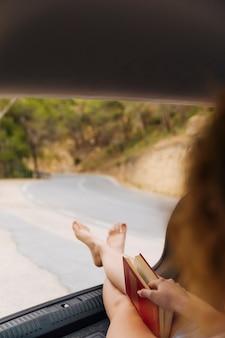 Piedi della donna dal bagagliaio della macchina