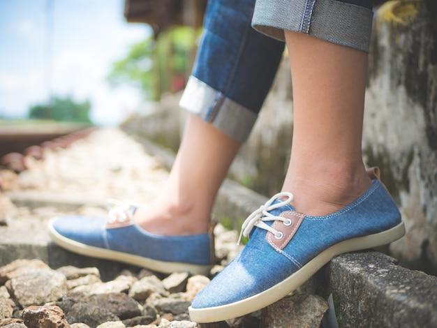 Piedi della donna del primo piano in scarpe da tennis blu che si siedono dalla ferrovia.