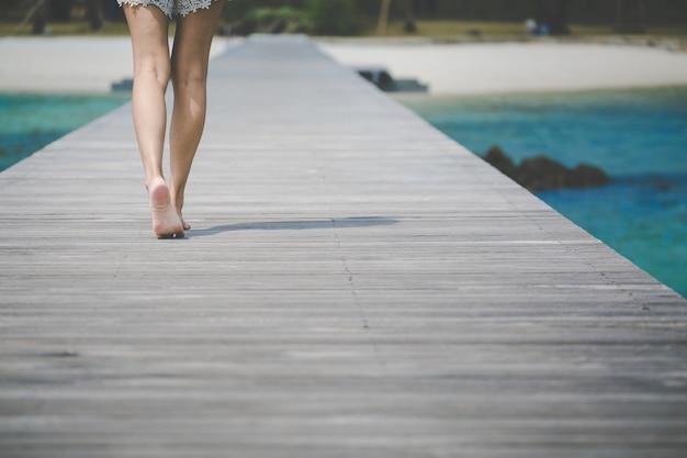 Piedi della donna di viaggio sul ponte di legno