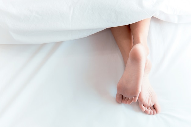Piedi della donna sul letto sotto coperta bianca. dormire e rilassarsi concetto